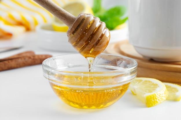 Cucchiaio caldo dorato del miele della ciotola di vetro dell'ingrediente della bevanda di autunno naturale dorato del miele stagionale