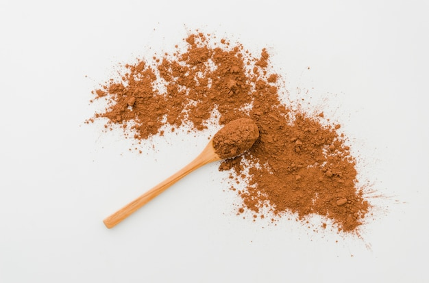 Cucchiaio con cacao in polvere su sfondo bianco