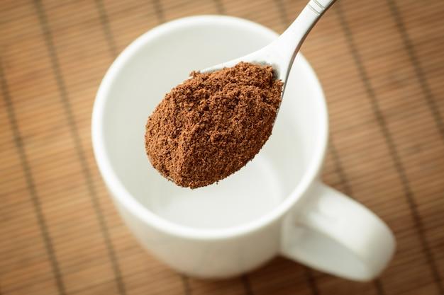 Cucchiaio con caffè vicino alla tazza bianca
