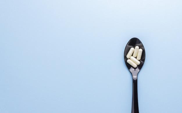 Cucchiaio con pillole su un tavolo blu. medicinale. farmaco. salute.