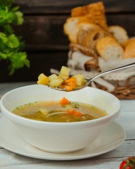 Cucchiaio con zuppa di pollo con verdure e aneto