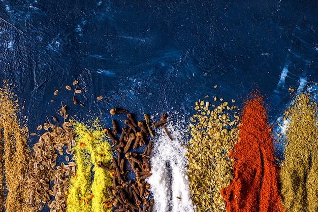 Cucchiaio d'annata dei semi di cumino della paprica del sale della paprica del sale dello zenzero della cannella dello zenzero del pepe della curcuma varie spezie sulla tavola. vista dall'alto spezie indiane