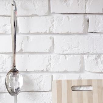 Cucchiaio del metallo che appende sul muro di mattoni bianco