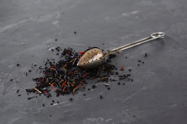 Cucchiaio del primo piano coperto di erbe del tè