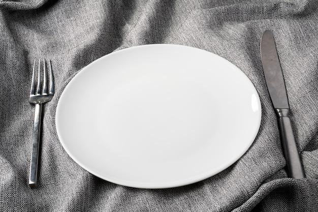 Cucchiaio della forchetta del piatto sul fondo dei vestiti del tessuto chiaro e senza profondità di campo