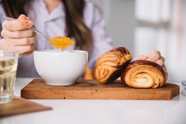 Cucchiaio della tenuta della donna con inceppamento vicino ai panini