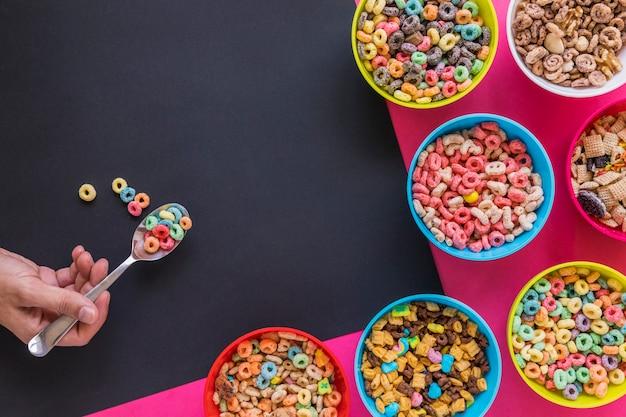 Cucchiaio della tenuta della persona con il cereale sopra la tavola
