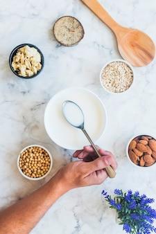Cucchiaio della tenuta della persona con latte sopra la ciotola sul tavolo