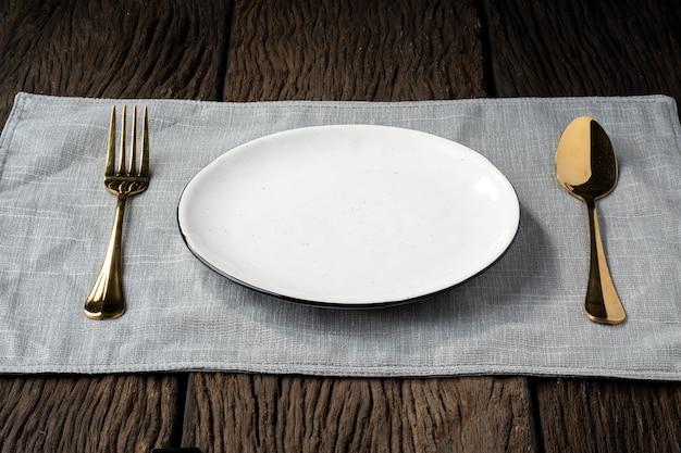 Cucchiaio di forchetta piatto su fondo in legno chiaro e senza profondità di campo
