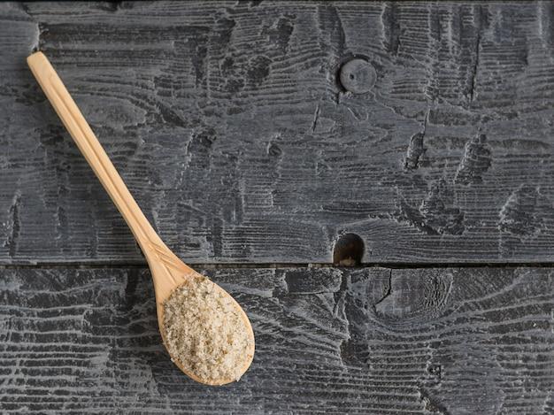 Cucchiaio di legno chiaro, riempito di sale con erbe sul tavolo di legno d'epoca.