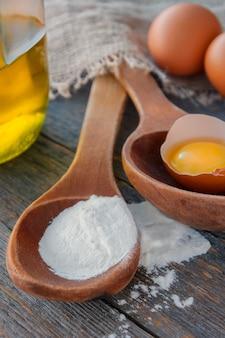 Cucchiaio di legno con farina, uova e una bottiglia di olio