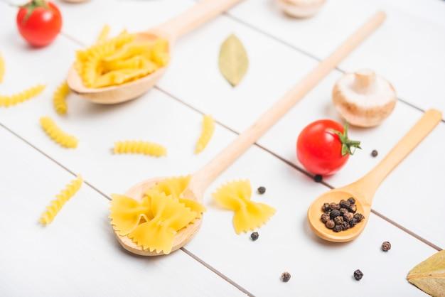 Cucchiaio di legno con fusilli di pasta; farfalle e pepe in grani con pomodoro; fungo; foglia d'alloro