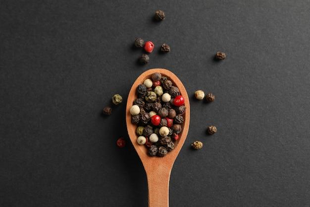 Cucchiaio di legno con la spezia del pepe su fondo nero, vista superiore