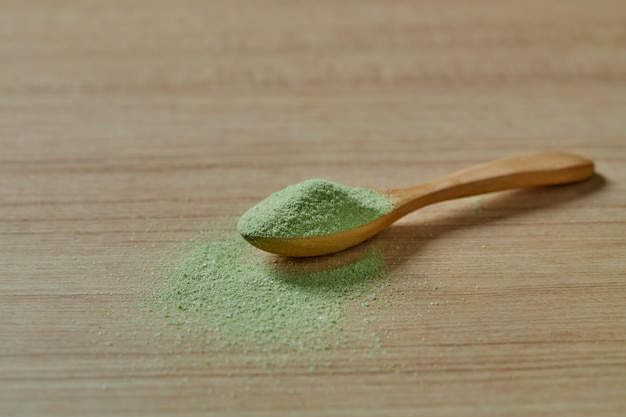 Cucchiaio di legno con tè verde matcha in polvere