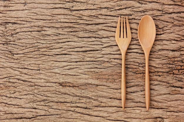Cucchiaio di legno di vista superiore, forcella sul pavimento di legno astratto con lo spazio della copia.
