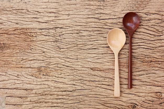 Cucchiaio di legno di vista superiore sul pavimento di legno astratto con lo spazio della copia.