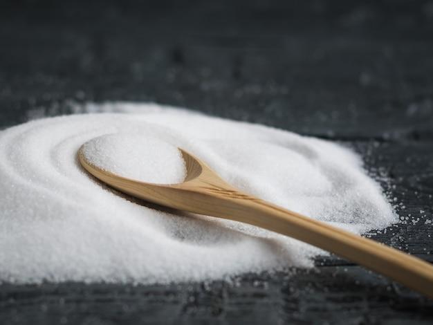 Cucchiaio di legno leggero riempito finemente di sale.