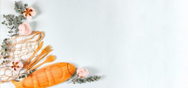 Cucchiaio di legno naturale eco, forchetta, coltello, piatto, rete a sacco, foglie di eucalipto e fiori di cotone su sfondo chiaro