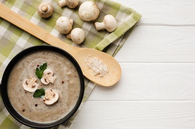 Cucchiaio di legno piatto e bisque di funghi con funghi