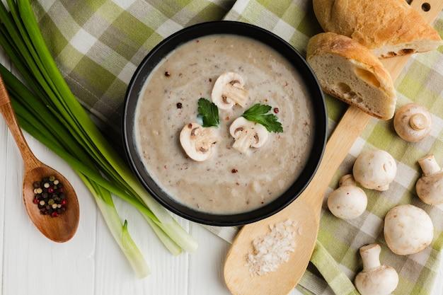 Cucchiaio di legno piatto e zuppa di funghi con pane e funghi