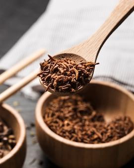 Cucchiaio di legno pieno di insetti fritti