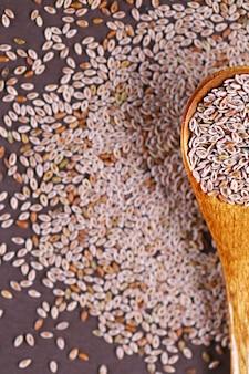 Cucchiaio di legno pieno di semi di piantaggine indiano su uno sfondo marrone scuro