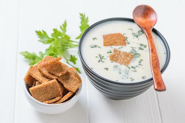 Cucchiaio di legno scuro sulla ciotola con crema zuppa di cavolfiore sul tavolo bianco.