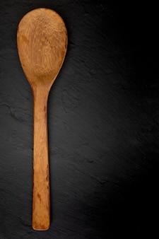 Cucchiaio di legno sull'ardesia nera con struttura.