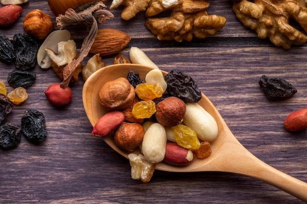 Cucchiaio di legno vista dall'alto con noci e uvetta arachidi e mandorle su un tavolo di legno