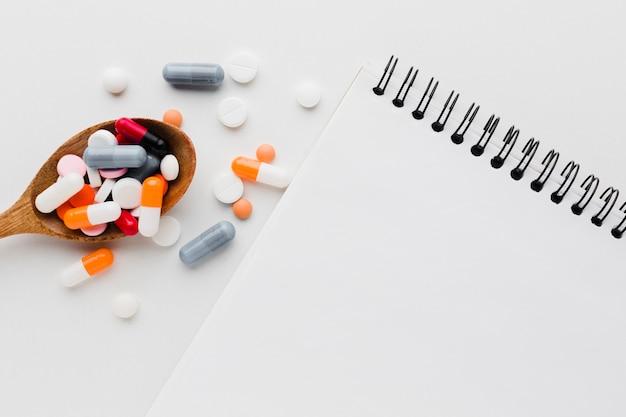 Cucchiaio di legno vista dall'alto pieno di pillole e blocco note