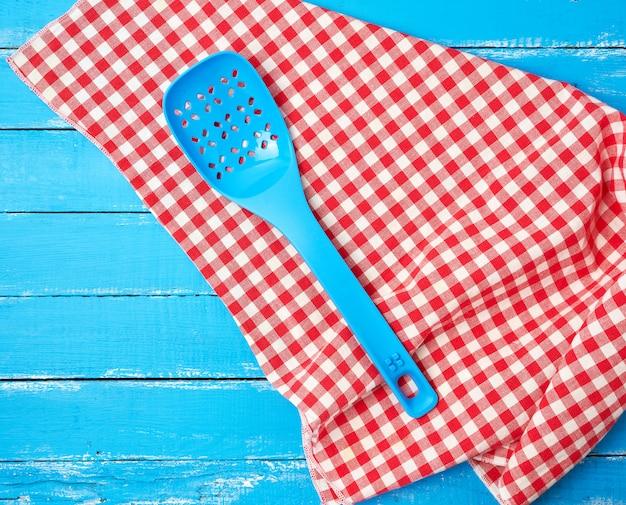 Cucchiaio di plastica blu con fori su un tovagliolo di tessuto rosso