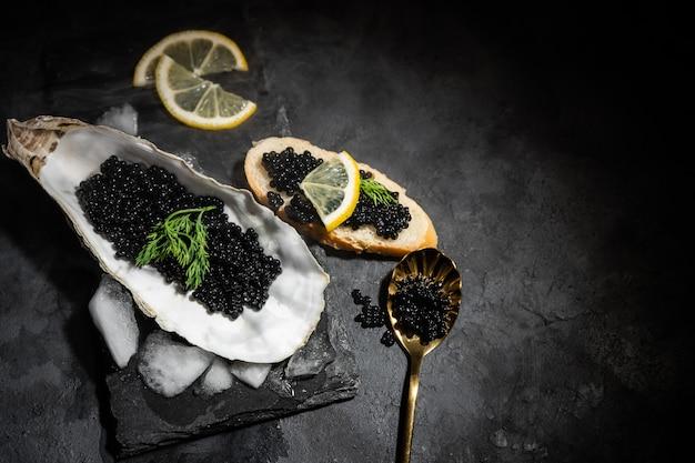 Cucchiaio dorato d'annata con il caviale e l'ostrica neri dello storione sulla tavola di pietra nera dell'ardesia. copia spazio