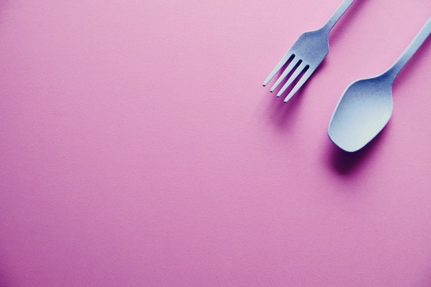 Cucchiaio e forchetta blu di plastica su fondo rosa