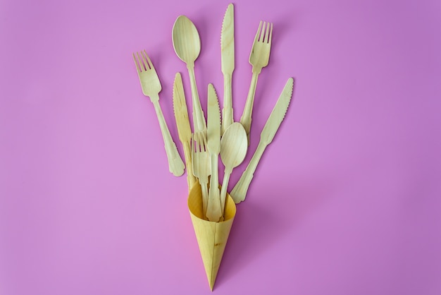 Cucchiaio e forchetta di bambù in fila su sfondo rosa o viola