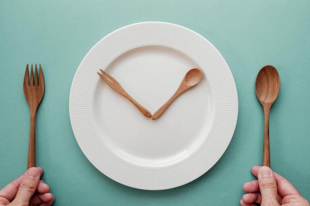 Cucchiaio e forchetta di legno come lancette di un orologio sul piatto bianco