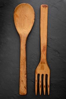 Cucchiaio e forchetta di legno sulla lavagna nera strutturata. spazio per inserire qui il testo. lettera per i ristoranti. (concetto di cibo di cucchiaio, pentola).