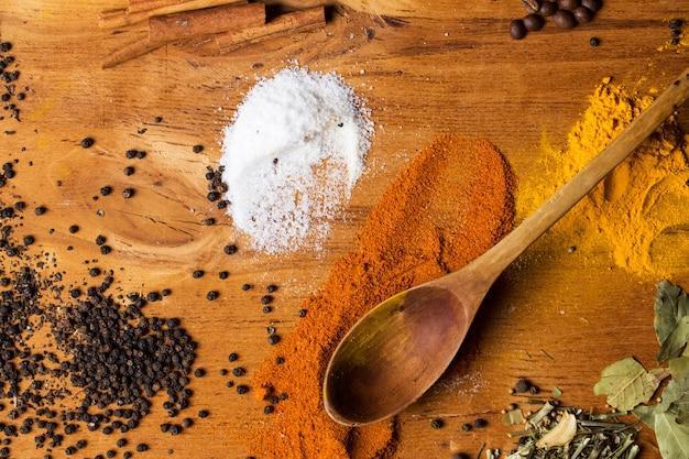 Cucchiaio e mucchio di spezie sul tavolo