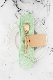 Cucchiaio e tovagliolo dorati legati con corda sul piatto bianco contro il contesto strutturato