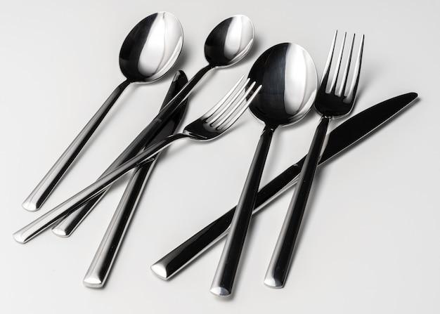 Cucchiaio, forchetta e coltello su uno sfondo bianco