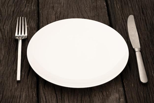 Cucchiaio forchetta piatto su legno chiaro e senza profondità di campo
