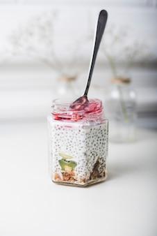 Cucchiaio inserito nel barattolo di vetro trasparente su sfondo bianco