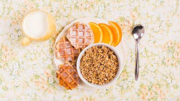 Cucchiaio; lanciatore di latte e piatto di ciotola di muesli sano con cialde e fetta di arance su sfondo floreale
