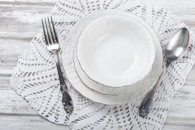 Cucchiaio, piatti bianchi e forchetta