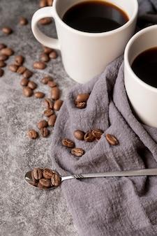 Cucchiaio pieno di chicchi di caffè e tazze