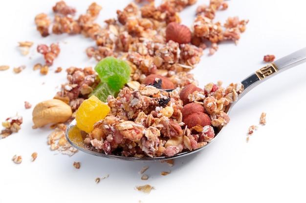 Cucchiaio pieno di granola isolato su fondo bianco