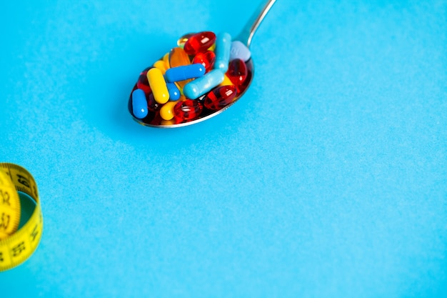 Cucchiaio pieno di pillole per la perdita di peso sul blu