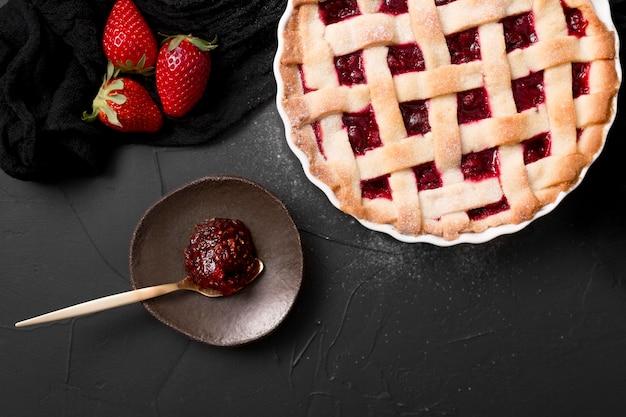 Cucchiaio riempito con marmellata di fragole e torta piatta disteso