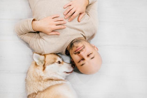 Cucciolo adorabile del husky e uomo sorridente felice che si trovano insieme sul pavimento.