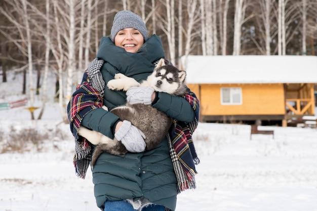 Cucciolo sorridente della tenuta della donna all'aperto