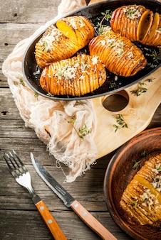 Cucina casalinga tradizionale americana. la dieta vegana patata hasselback fatta in casa con erbe fresche e formaggio. sul vecchio tavolo di legno, copia spazio